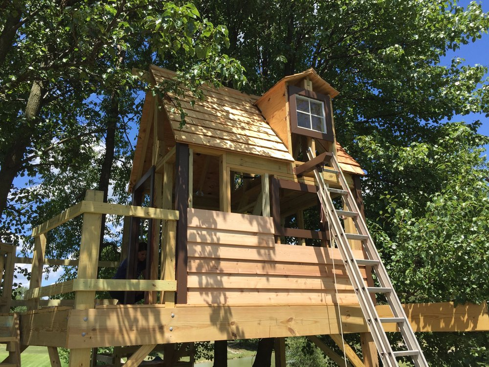 Cedar siding being attached to the front of the clubhouse treehouse.