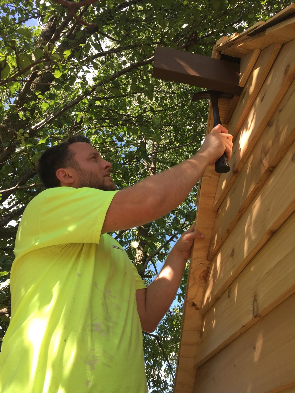 Installing the last piece of cedar siding for the clubhouse treehouse
