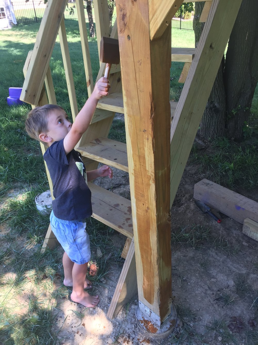My son staining the clubhouse treehouse