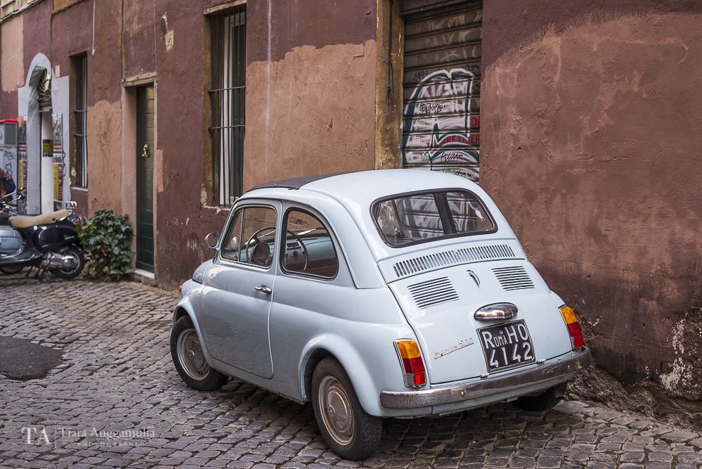 A light blue Nuova 500 Fiat parked on a street.