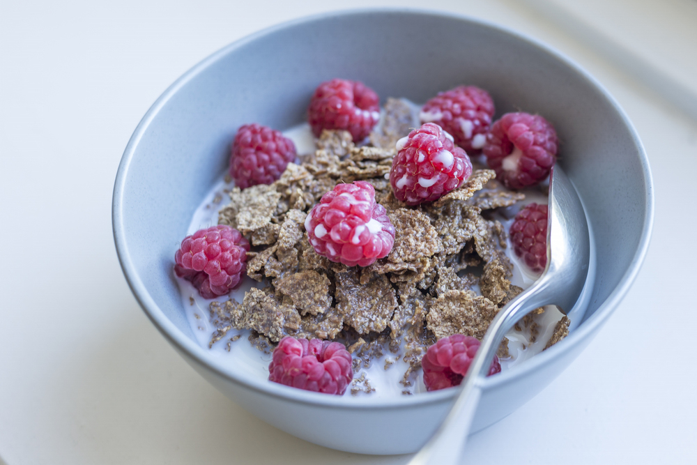 A bowl of bran flakes with fresh raspberries and milk.jpg