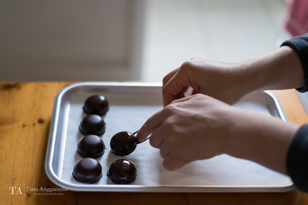 Raw bonbon on a tray after being dipped in dark chocolate.