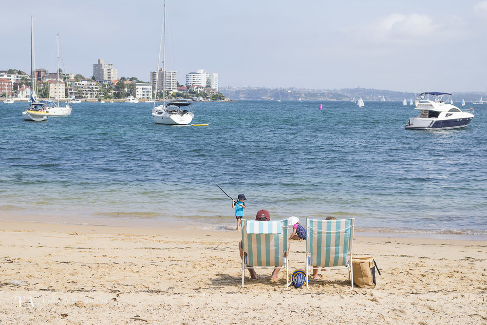 A family relaxing on Manly beach.