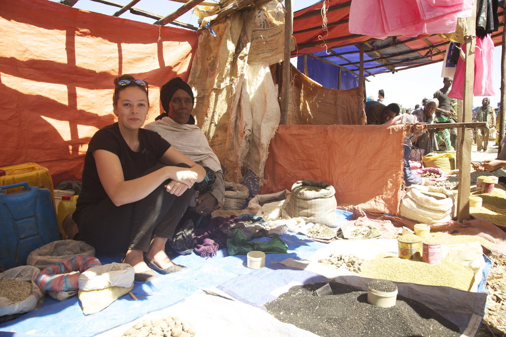"""Here I'm hanging out with a mother in our program. She sells tea and spices and incense at the Bekoji market. I was selling some spices with her to make people laugh at the market."""