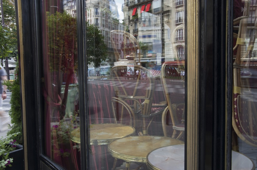 commenter >  La vitrine d'un café réfléchissant le boulevard du Montparnasse  < comment