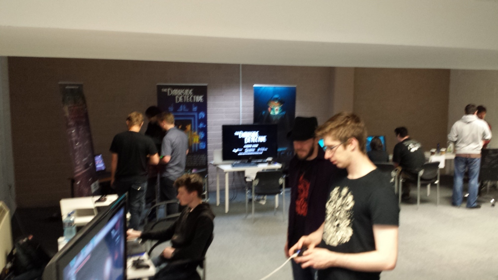 Indie gamers show their wares, with Onikira on the big screen, and Goblin's Grotto, Darkside Detective and Trench visible in the background.