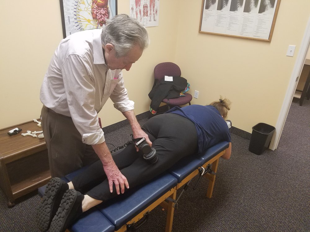 Bert performing a chiropractic massage on a patient to loosen the muscles