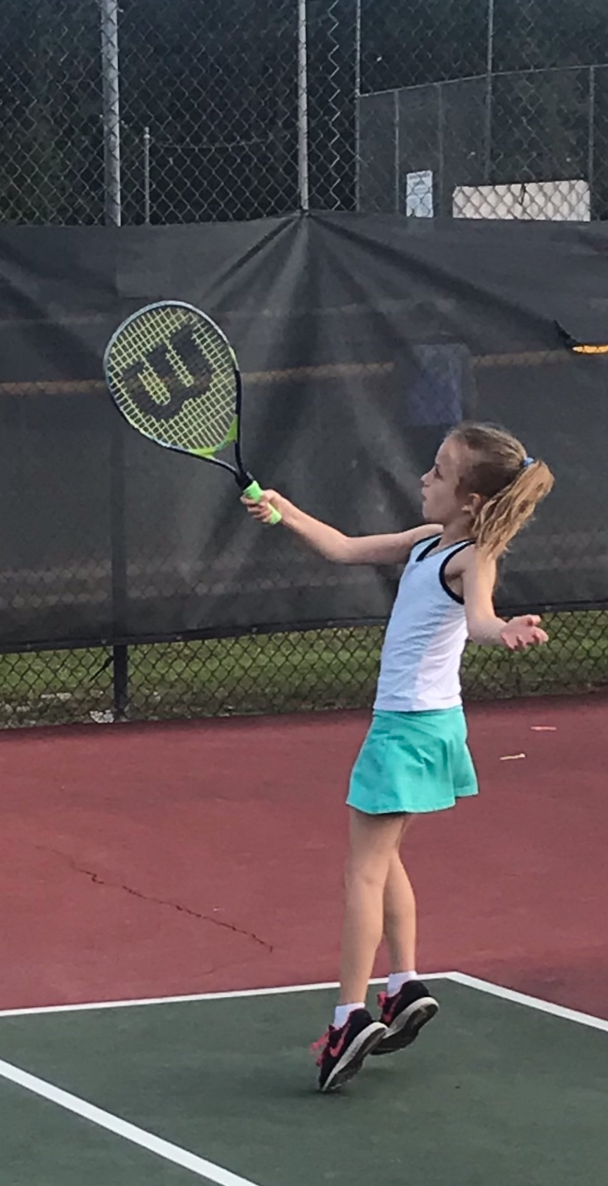 Caroline reaching for a high forehand return.