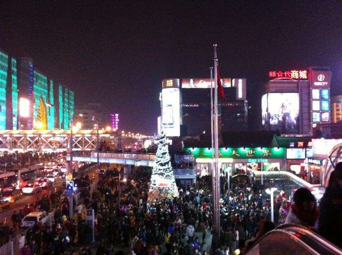 This is Xidan, one of several shopping districts in Beijing. You can't see from the picture, but   people write their Christmas wishes on strips of colored paper and hang them on the branches of the Christmas tree in the center  . This brings to mind a similar practice   in Japan where it is customary to do the same to trees in the compounds of temples.