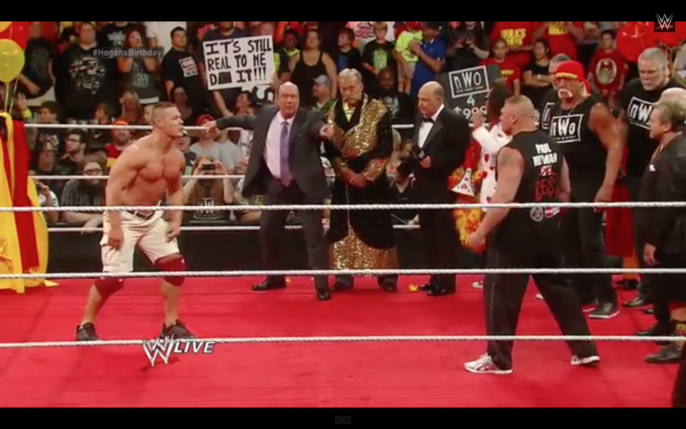Cena removes his wrists-bands and arm-bands, making ready to fight Lesnar.