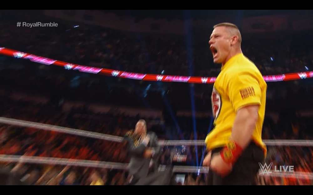Obscured here, but Heyman is in the corner clutching the championship for dear life.