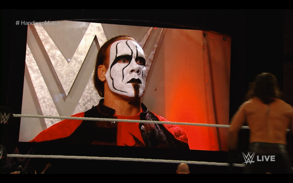 Sting appears ominously on the Titantron, the WWE logo behind him. He resembles a ghostly propaganda poster from some alternate World War II reality. The image speaks for itself.