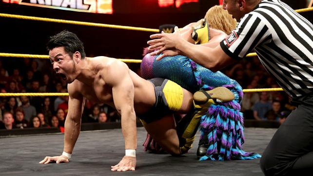 Hideo Itami tries to break a submission hold.