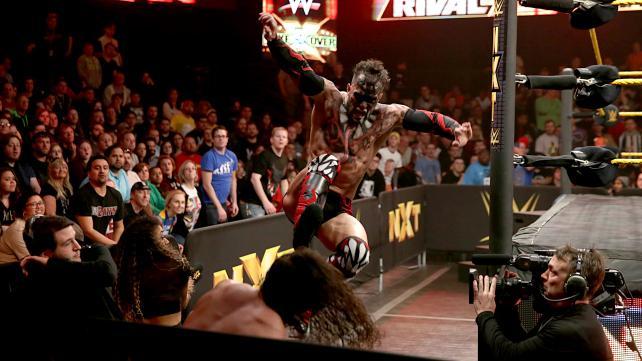 Finn Balor gives Adrian Neville a flying kick through the barricade.