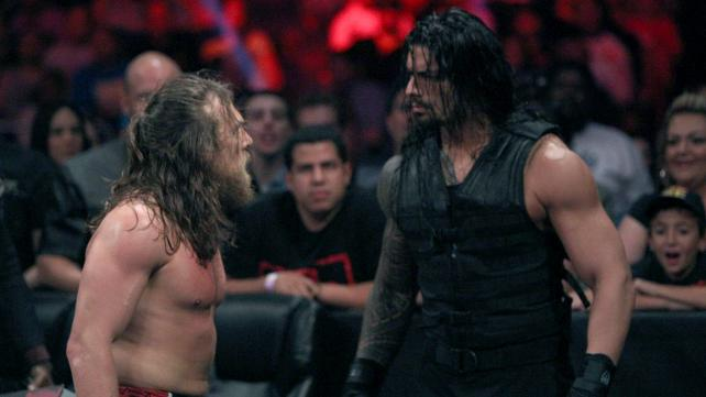 Roman and Daniel stare-down at ringside.