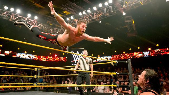 Sami Zayn soars over the top rope.