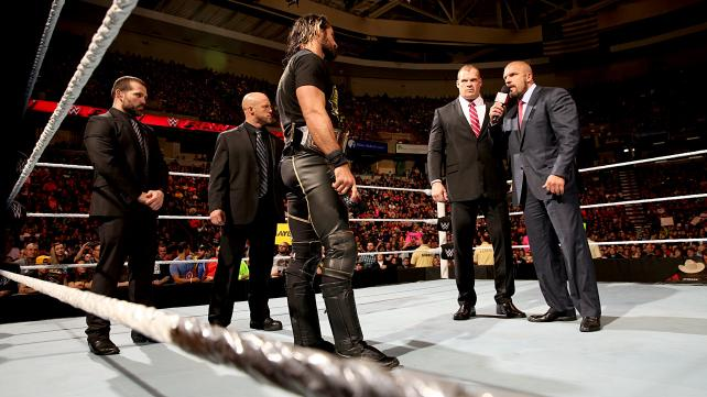 Kane, Triple H, and Seth Rollins confer in the ring on Monday Night Raw.