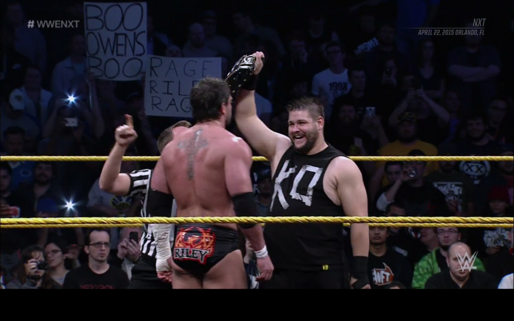 Kevin Owens grinning at Alex Riley in the main event.