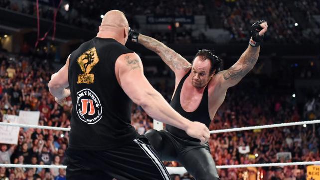 Undertaker kicking Brock between the legs.
