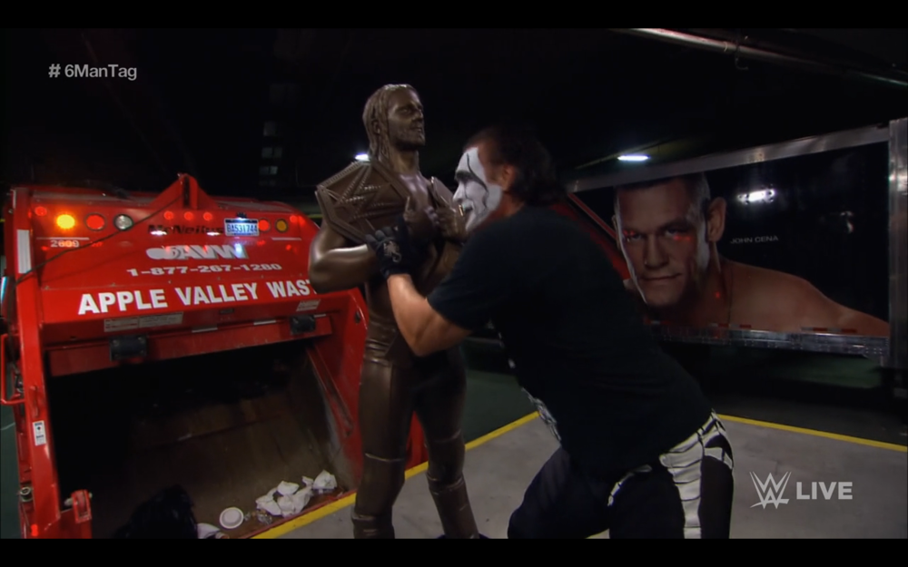Sting pushes a statue of Seth Rollins into a garbage truck.