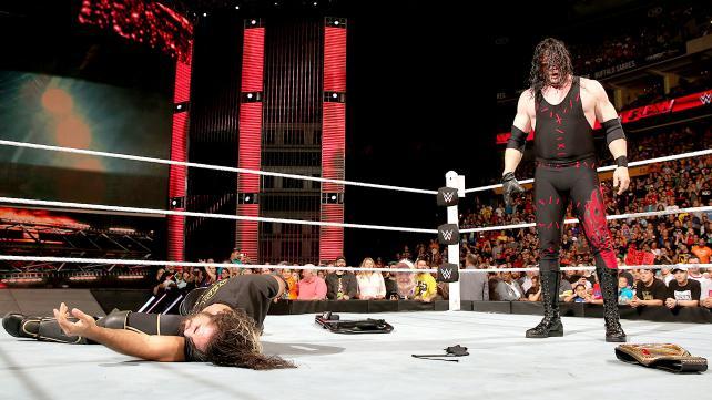 Kane chokeslams Seth Rollins.
