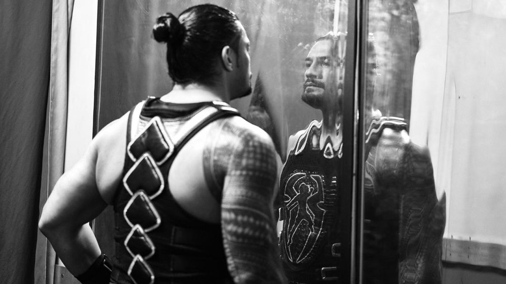 Roman Reigns backstage, looking in the mirror.