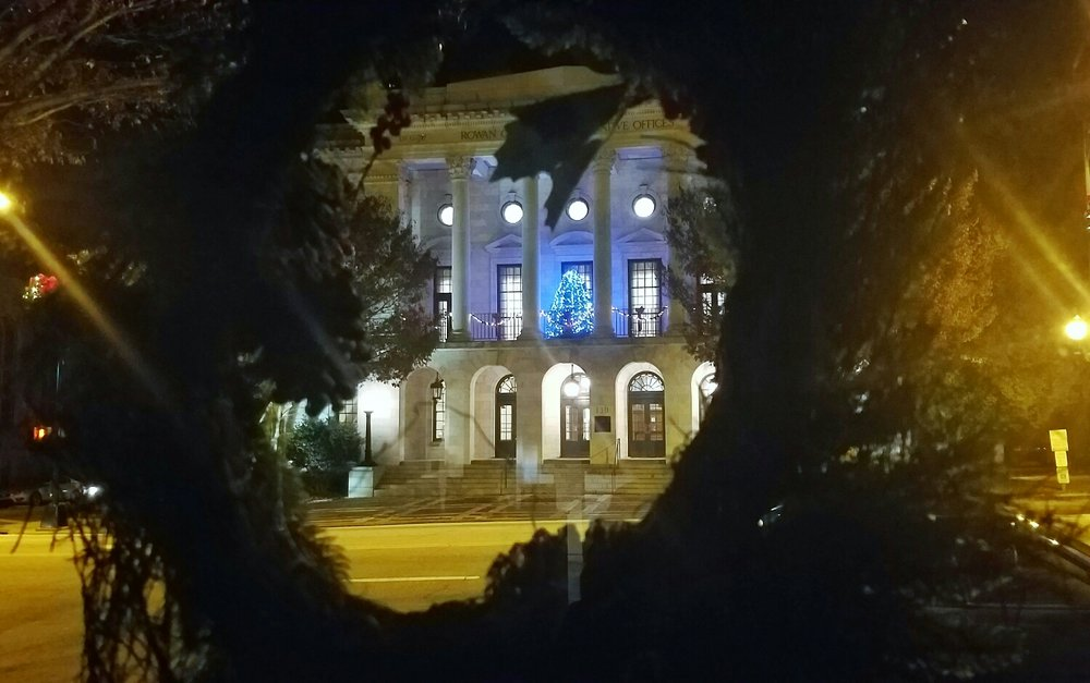 An illuminated Christmas tree sits on the deck of the Rowan County Administration Building in Salisbury NC. Smartphone picture through a wreath on the door of the Salisbury Post.
