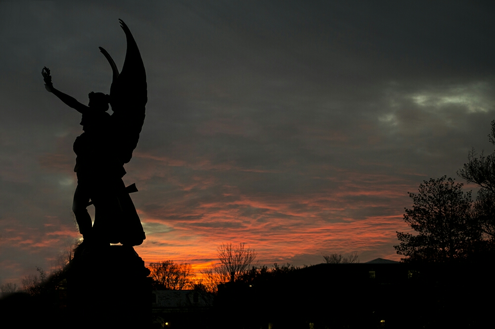 "The sun sets behind an angel statue in downtown Salisbury, N.C. The Statue is known by the name ""fame."" It's honors soldiers who fought in the Civil War. Taken with my DSLR."