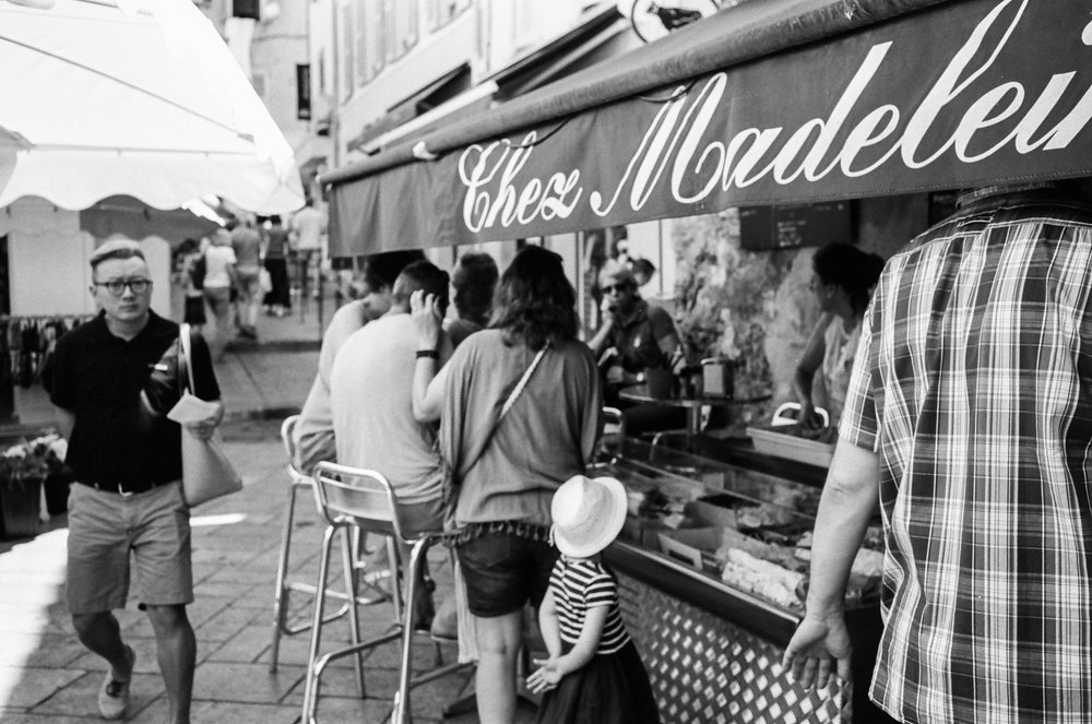 A young girl waits patiently for her order, St. Tropez. France. 2016.
