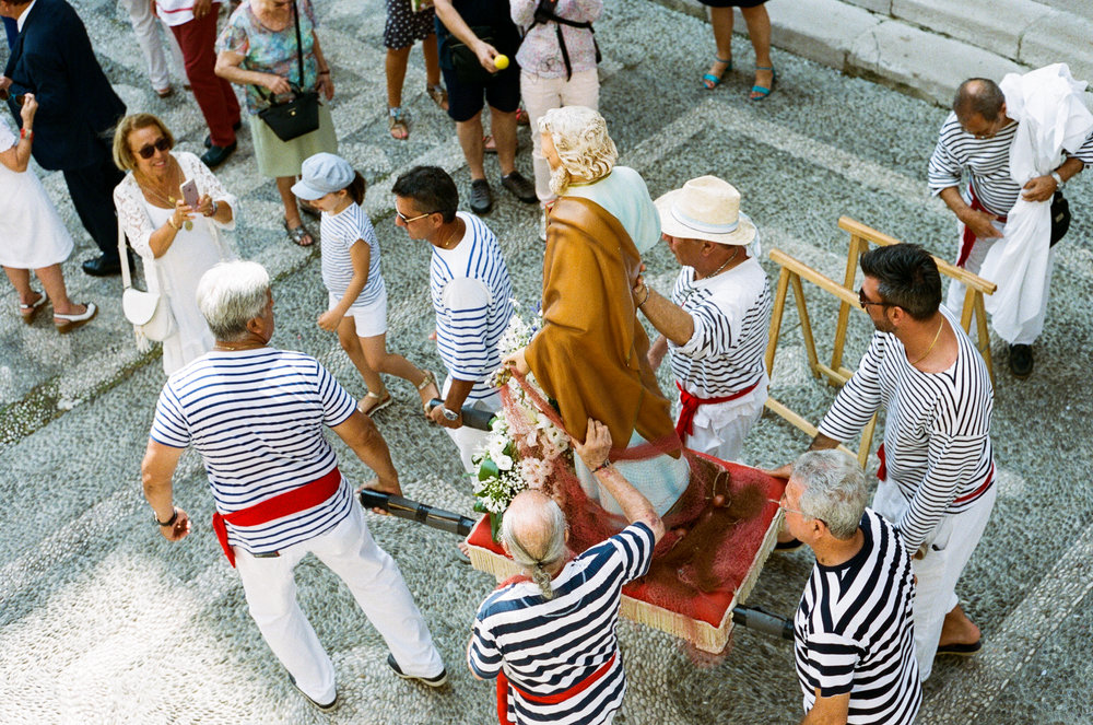 Locals dressed in traditional fish attire carry a statue of Christ down towards the seafront. Menton. 2018.