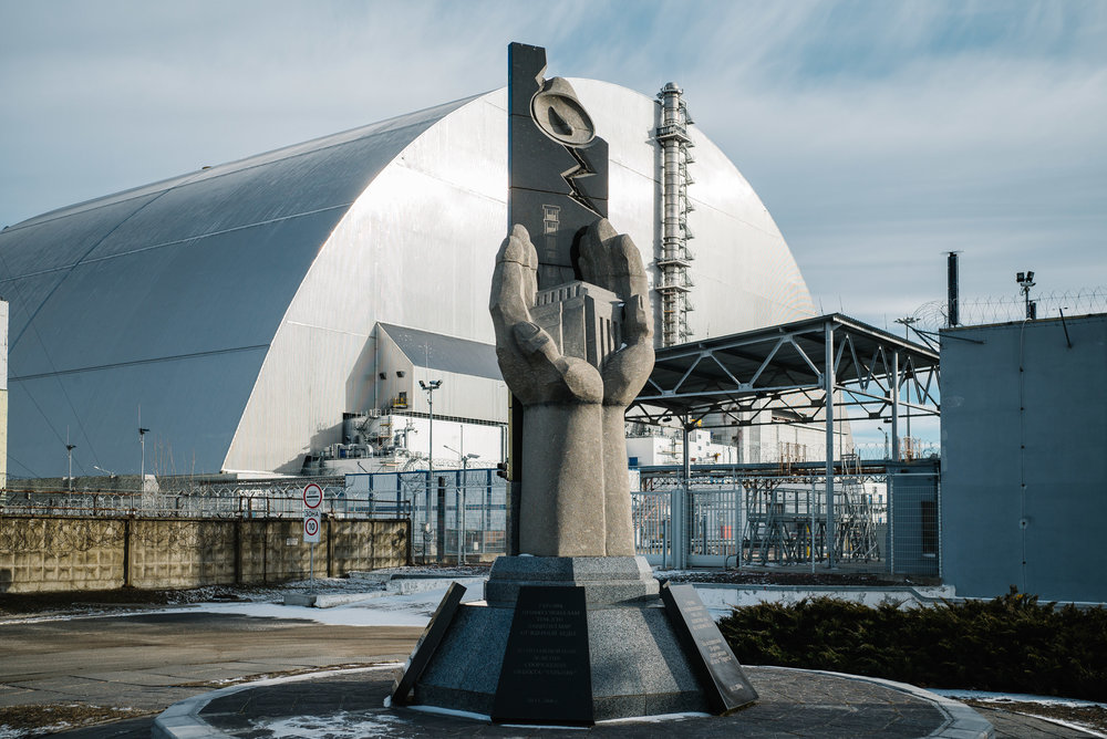 The New Safe Confinement which covers the damaged reactor 4 sits behind a monument to the builders of the original 'sarcophagus' which houses the derelict reactor - Clifford Darby 2019