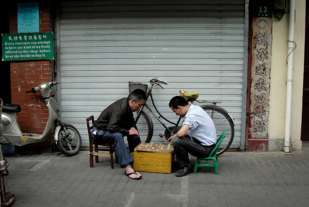 "Men playing board games outside a closed tea shop. The sign says ""Every customer can attempt to have any kind of tea freely offered in this shop before he or she can decide to buy it."""