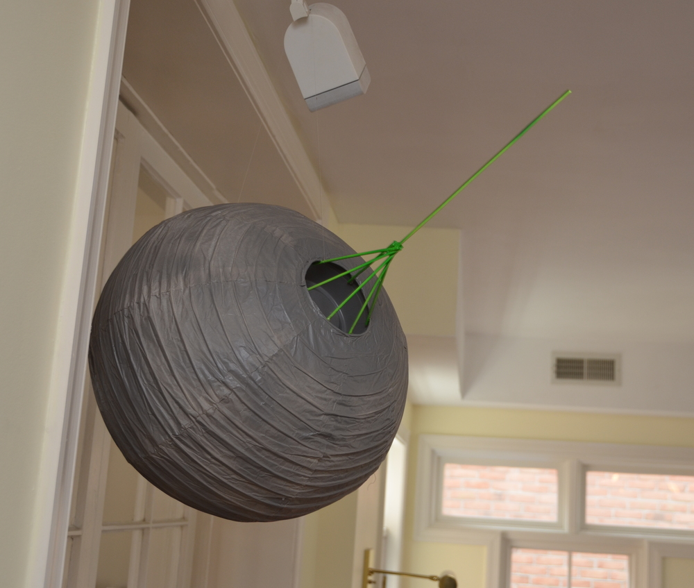 "16"" paper lantern painted gray; plastic Whole Foods container glued into the lantern hole and attached to a wooden, painted-green array of wooden dowels."