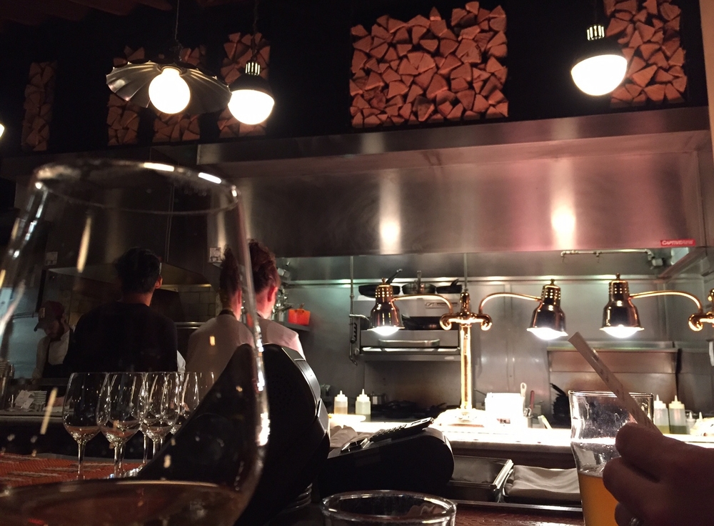 view, through my wine glass, of part of The Red Hen's kitchen