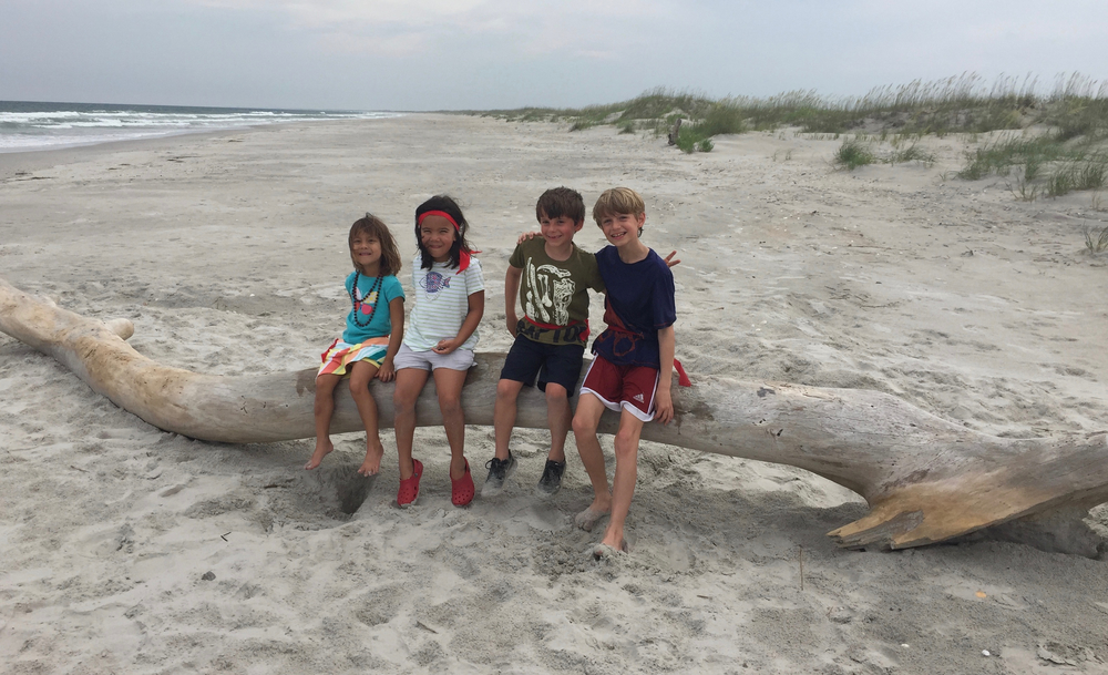 Cousins on a sizeable piece of driftwood