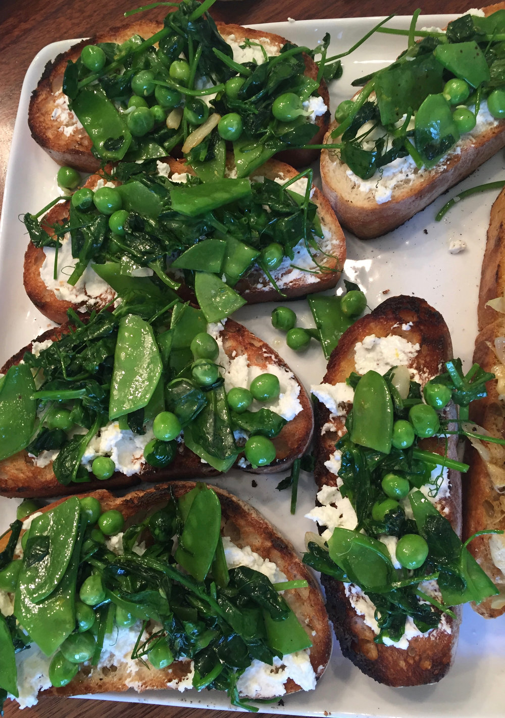 Thank god spring is (nearly) here. Grilled bread with ricotta, lemon zest, olive oil, salt and sauteed pea shoots, snow peas, and English peas is fab.