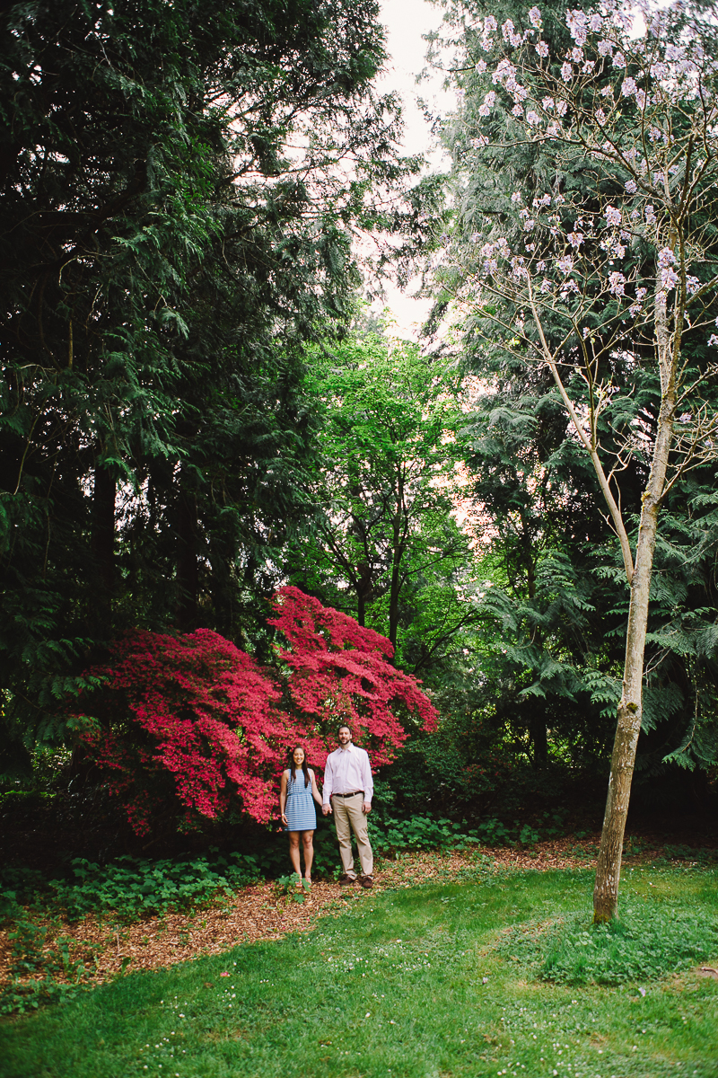 an engaged couple standing in front of a flowering tree in the woods. image by Love Song Photo