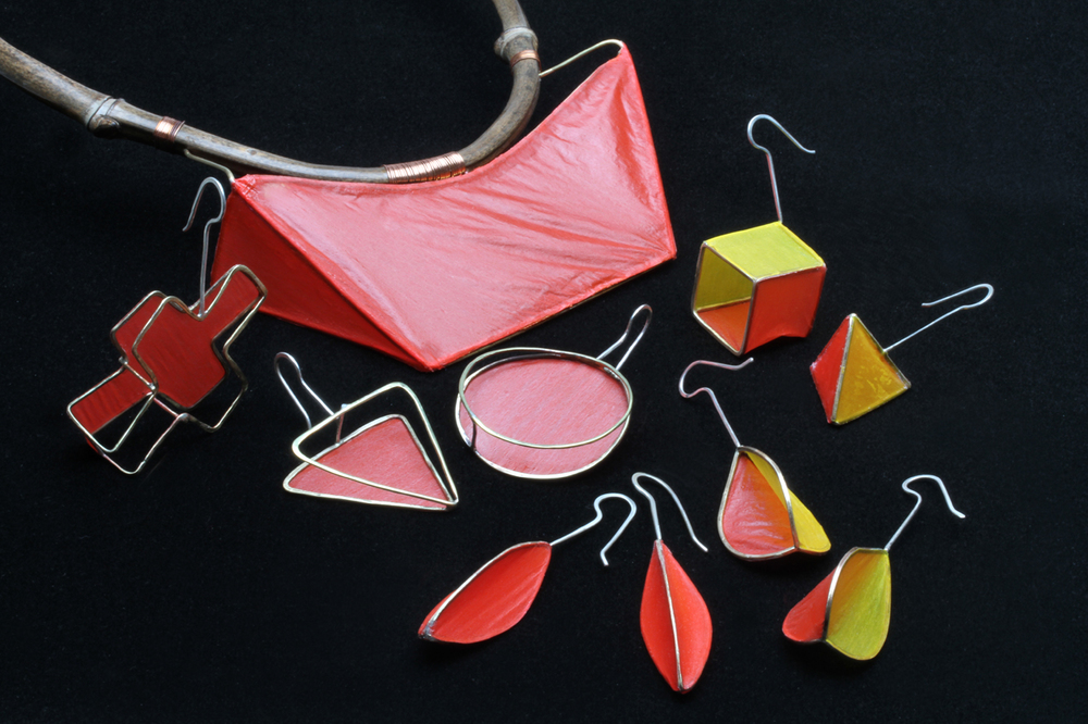 COVERLITE MATRIX PENDANT ON HEATBENT BAMBOO TORQUE AND WIRE MATRIX EARRINGS, some of which are in sets of three, to be worn in different asymmetrical pairs, or are an asymmetrical pair, like the yellow/red cube and triangle. In foreground are two pairs of symmetrical Pod earrings, with all red or red/yellow Coverlite skins. Earrings are 5.0-7.5 cm long and weigh between 1.6 to 3.1 grams each, all from 2014.