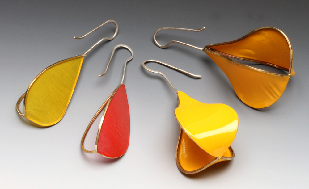 POD MATRIX EARRINGS WITH ONE COVERLITE PANEL AND FIG/PEAR-SHAPE MATRIX EARRINGS WITH TWO ULTRACOTE PANELS, from 2014/2015, demonstrating matte and shiny surfaces respectively, as well as how they react to heat. Heatgun on highest setting used for both. Fig/pear-shaped earrings are 7.2 cm high. All my earrings are supposed to be worn with open end of earwire facing inward. These were photographed with a macro lens, with studio strobe, on a Varitone background (Liu 2014b).