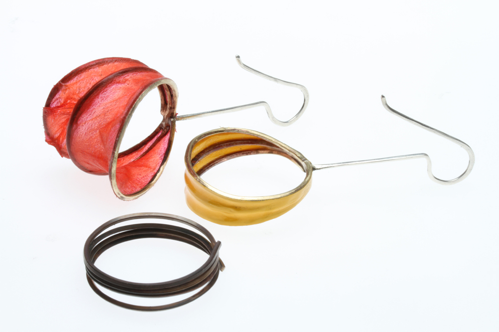 COMPARISON OF COIL EARRINGS WITH COVERLITE OR ULTRACOTE, where they are soldered together at the top to the silver earwire. Then the bottom is spread or pulled apart. The dark, wound brass coils used to form the matrix have been formed on a wood mandrel, then annealed so that they are easier to work.