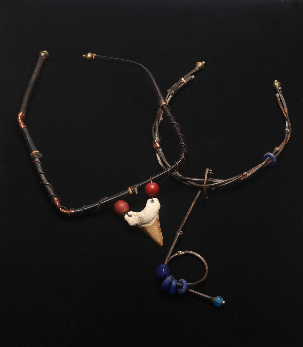 SQUARE BEND TORQUE WITH FOSSIL SHARK TOOTH VS INTERTWINED TORQUE AND PENDANT, latter with freshly cut black bamboo culms. Note how tight the intertwining, as well as the bail of the pendant is also a tight radius bend. This torque is decorated with vintage Bohemian glass rings and beads from the African trade, and Baule brass bead terminations. The 45-70 million years old fossil  Lamna  shark tooth from Morocco is accentuated with two Cornaline d' Allepo Venetian beads, which simulate the way Polynesians use red sealing wax to decorate their shark tooth jewelry. The tooth is attached to the bamboo with wrapped, annealed square bronze wire.  All photographs by Robert K. Liu/Ornament.
