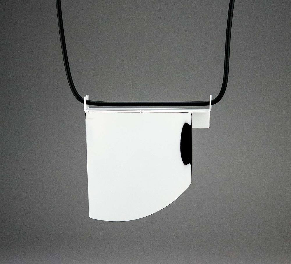 FOLD 1 NECKLACE by Jim Bové of sterling silver, rubber cord, industrial auto paint on copper, 10.8 x 10.16 x 1.27 centimeters, 2015.  Photograph by Jim Bové.