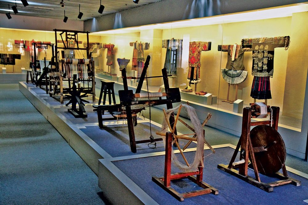 CLOTHING GALLERY, with spinning fixtures and weaving looms in foreground. Such textile furniture has also been preserved in other museums.  Photographs by Robert K. Liu and Patrick Benesh-Liu/ Ornament; shot hand-held, with high-ISO and no flash, to prevent light damage.