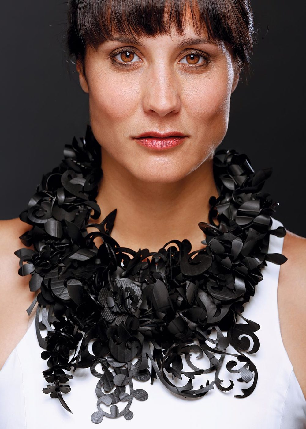 KATHLEEN NOWAK TUCCI. Secret Garden Necklace of recycled motorcycle and bicycle inner tubes and Nespresso coffee capsules, Second Place Alternative Metals/Materials.