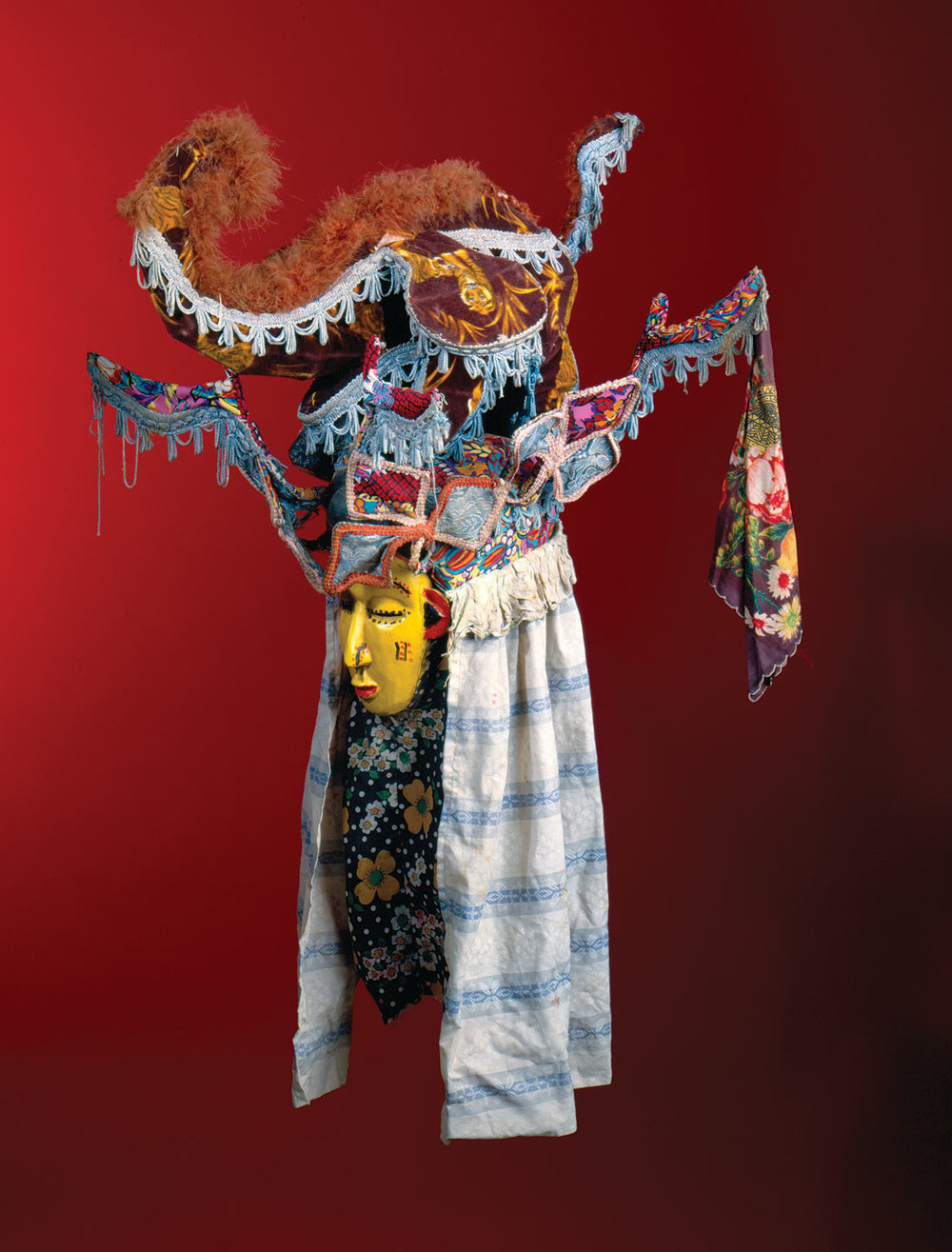 MASQUERADE HEADDRESS of wood, pigment, wire, fabric, fringe, braid, polyurethane foam, metal, 58.4 x 55.9 x 68.6 centimeters, Freetown, Sierra Leone, circa 1970s.  Images courtesy of the Fowler Museum at UCLA.