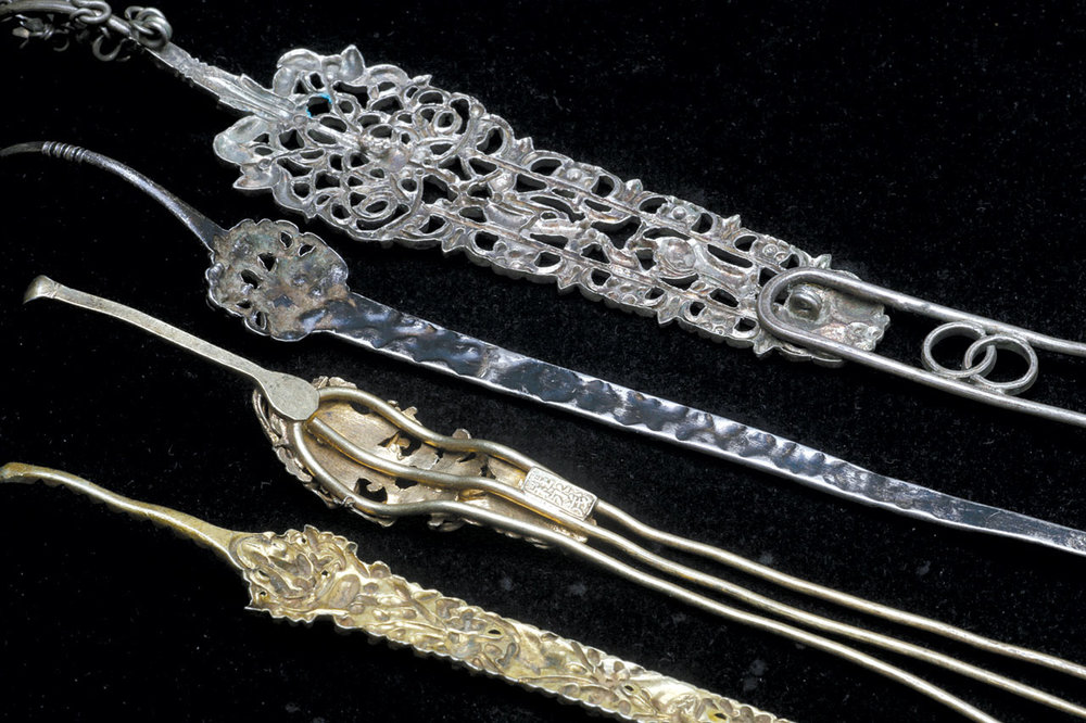 REVERSE OF THESE HAIRPINS WITH EARPICKS, clearly demonstrating use of dies on three. Note how cleanly the top specimen has been pierced and filed, whereas the bottom specimen is also diestruck but not pierced. The topmost specimen also has an elaborate dangle attached. The hairpin second from the top has its upper part diestruck, while the tine is of thicker silver that has been repouseed. The three tine hairpin is fabricated and has a separate plaque with a hallmark. While we do not know the types of heat sources used for manufacture of such hair ornaments, it is likely a mouth blowpipe was employed for soldering.