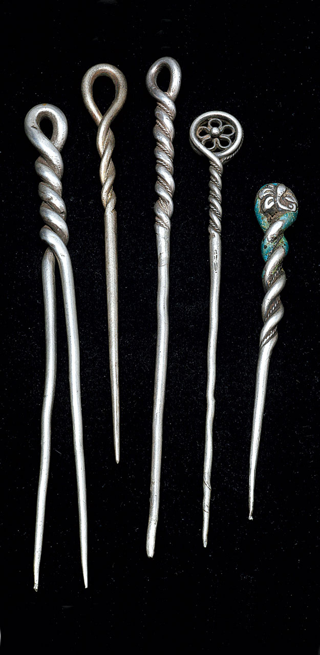 SINGLE AND TWO TINE TWISTED SILVER HAIRPINS, which offer a clue on how these twisted hair ornaments were made. Two strands of silver wire were twisted, soldered, then filed or hammered into a tapered single tine ( pers. comm ., Harold O' Connor, 1/2017). With such thick wire, it would take considerable filing to reduce the twisted silver to a thin taper. Tine of second to right example shows remnants of twisting. Three pins had beaded wire added while being twisted and two have additional decorations on the loop, including enameling on one. Size range 8.5 to 12.0 centimeters long, with largest seen 18.0 centimeters long.