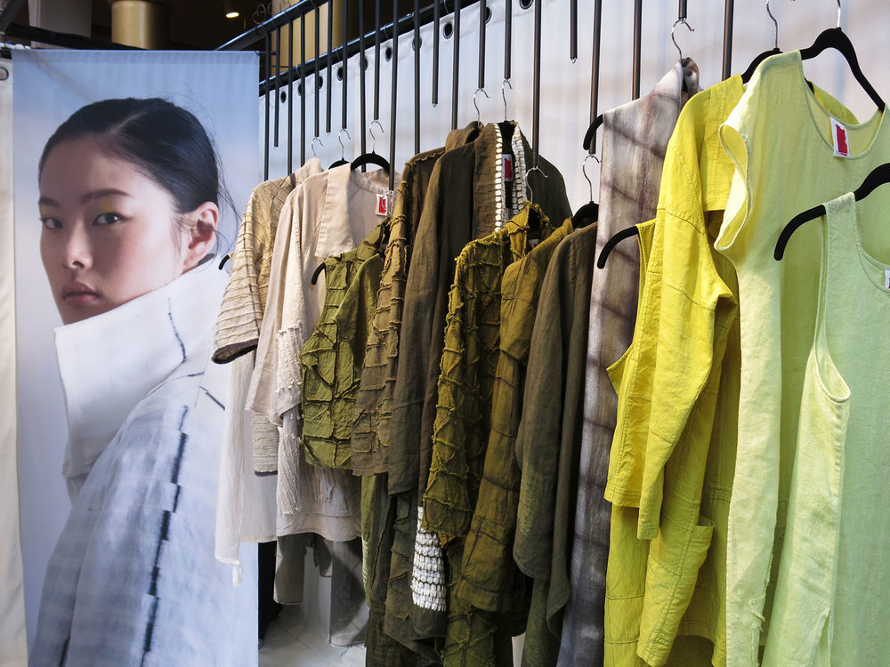 Clothing artist  Amy Nguyen 's booth, featuring a palette of green colors. This year Amy felt particularly compelled to create work in some shade of green, as a comfort and an anchor. She went through more than ninety combinations of dyes trying to find just the right color.