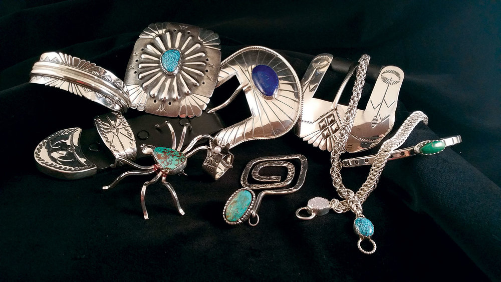 JEWELRY BY JERRY E. GAUSSOIN JR. (left to right, top to bottom): Navajo Mother Earth bracelet, 2017; Navajo Four Cardinal Directions concho style buckle, 2017; Ranger belt buckle, 2015; Simplicity cuff, 2017; Navajo Spider brooch, 2014; Pueblo Protector ring, 2017; Pueblo Maiden pendant, 2017; Byzantine Chain bracelet, 2017; and Half Persian chain bracelet, 2017. All jewelry is fabricated, some hand-stamped, formed and/or textured, set with turquoise or lapis. Photograph by Jerry E. Gaussoin Jr.