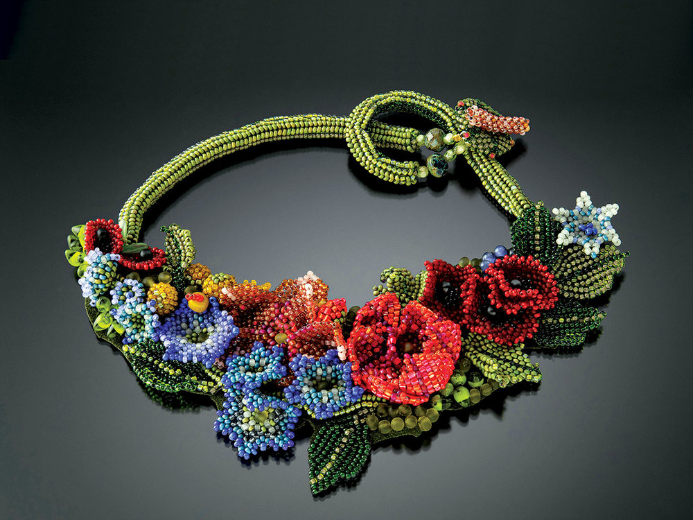 BLUEBELLS AND POPPIES FIORI NECKLACE of glass beads, woven in various off-loom stitches with a needle and fishing line in a free-form style. Petals and leaves are woven and then embroidered to each other and a fabric base. Embellished with stones and fire-polished glass, the necklace is backed with Ultra-suede; back of necklace is created with a filled herringbone spiral tube, 43 centimeters long x 9 centimeters high, 2014.